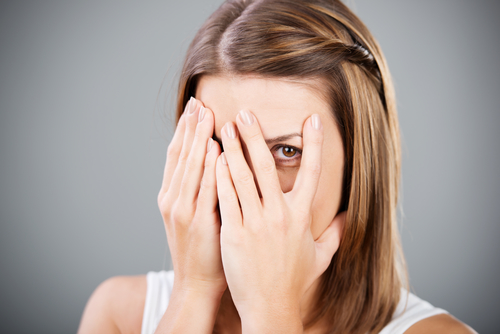 Beautiful cheerful female covering her face using hands